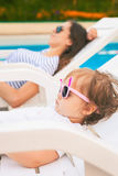 Endless summer Cute baby relaxing at sunbed near pool, resort. Stock Images