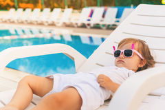 Endless summer Cute baby relaxing at sunbed near pool, resort. Stock Photos