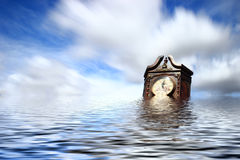Endless Time. Antique clock floating in a lake under wispy clouds Stock Photography