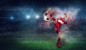 With endless will to victory. Mixed media. Kid boy in red uniform on soccer field. Mixed media Stock Photo