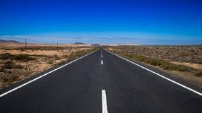 Endlose Straße gegen blauen Himmel Stockfoto