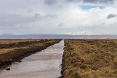 Endloser gerader Abzugsgraben, der durch großes Gebiet zum entfernten Gebirgszug mit Schnee, Eis und Gletscher auf Horizont fegt Stockbilder