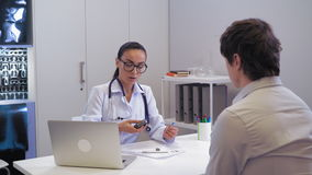 Endocrinologist explain man how measure blood sugar. Young doctor showing patient how using home glucometer. Woman therapist wearing white coat sitting at the stock footage