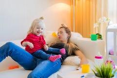 Endormi tombé par maman épuisé sur le divan photographie stock libre de droits