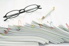Endroit de crayon et de lunettes sur la pile des écritures de blanc de surcharge Image stock