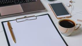 Endroit pour le texte sur le comprimé avec le papier, l'ordinateur portable, le smartphone et le café sur la table blanche Images stock