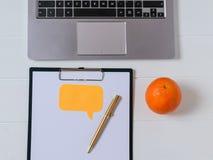 Endroit pour le texte sur le comprimé avec le papier, le stylo d'or, l'ordinateur portable et l'orange sur la table blanche Images libres de droits