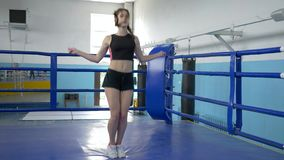 Endurance of body, sports female does skipping exercises on ring in gym. Endurance of body, sports female does skipping exercises on boxing ring in gym stock video footage