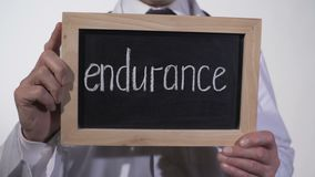 Endurance written on blackboard in doctor hands, hope for recovery, strength. Stock footage stock footage