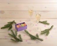 Endureça macarons com champanhe e ramo da árvore de Natal Fotografia de Stock Royalty Free