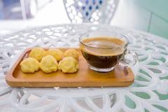 Endureça o eclair ou os sopros de creme ou o Profiterole com o copo de café na placa de madeira na tabela branca imagens de stock royalty free