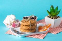 Endureça, os copos com café, cookies em um fundo brilhante Fotos de Stock
