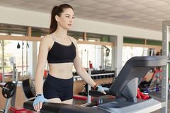 Enduring confident young lady starts training on treadmill, does cardio exercises, feels confident. Athletic slender girl wears royalty free stock photography