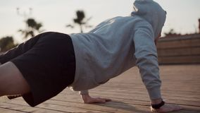 Enduring man is doing pushups in park area in city in daytime stock footage