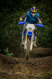 Enduro bike rider. On action. Small jamp on muddy terrain royalty free stock images