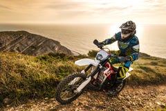 Enduro bike rider. Enduro rider climbing a steep slope against a beautiful sunset on a seascape Royalty Free Stock Image