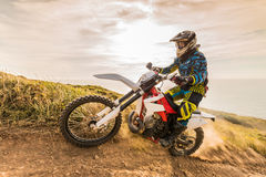 Enduro bike rider. Enduro rider climbing a steep slope against a beautiful sunset on a seascape stock photo