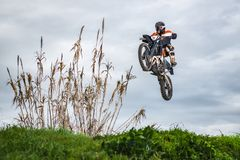 Enduro bike rider. In action. Jump on mud and grass terrain royalty free stock photos