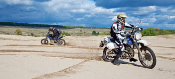 Enduro. Bike riders driving through the desert stock photos
