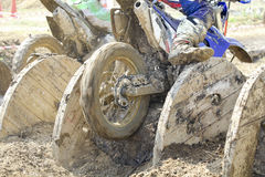 Enduro bikes pass obstacle cable drums in track. Stock Photos