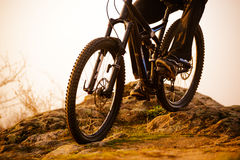 Enduro Cyclist Riding the Bike Down Rocky Hill at Sunset. Close up Extreme Sport Concept. Space for Text. Stock Images