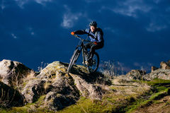Enduro Cyclist Riding the Bike on the Rock at Night. Extreme Sport Concept. Space for Text. Stock Photos