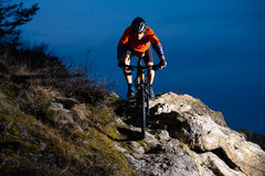 Enduro Cyclist Riding the Bike on the Rock at Night. Extreme Sport Concept. Space for Text. Stock Image