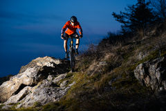 Enduro Cyclist Riding the Bike on the Rock at Night. Extreme Sport Concept. Space for Text. Stock Images