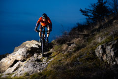 Enduro Cyclist Riding the Bike on the Rock at Night. Extreme Sport Concept. Space for Text. Royalty Free Stock Photography
