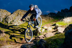 Enduro Cyclist Riding the Bike on the Rocky Trail at Night. Extreme Sport Concept. Space for Text. Royalty Free Stock Photos
