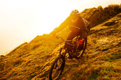 Enduro Cyclist Riding the Mountain Bike Down Beautiful Rocky Trail. Extreme Sport Concept. Space for Text. Stock Photography