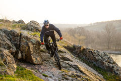 Enduro Cyclist Riding the Mountain Bike Down Beautiful Rocky Trail. Extreme Sport Concept. Space for Text. Stock Image