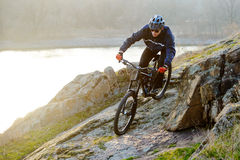 Enduro Cyclist Riding the Mountain Bike Down Beautiful Rocky Trail. Extreme Sport Concept. Space for Text. Stock Images