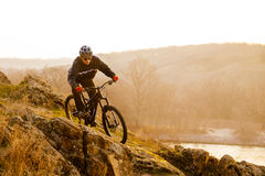 Enduro Cyclist Riding the Mountain Bike Down Beautiful Rocky Trail. Extreme Sport Concept. Space for Text. Stock Photo