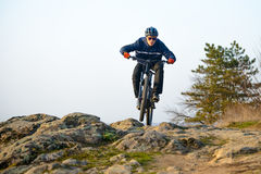 Enduro Cyclist Riding the Mountain Bike Down Beautiful Rocky Trail. Extreme Sport Concept. Space for Text. Stock Photos