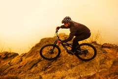 Enduro Cyclist Riding the Mountain Bike on the Rock. Extreme Sport Concept. Space for Text. Royalty Free Stock Image