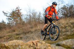 Enduro Cyclist Riding the Mountain Bike on the Rocky Trail. Extreme Sport Concept. Space for Text. Stock Image