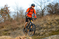 Enduro Cyclist Riding the Mountain Bike on the Rocky Trail. Extreme Sport Concept. Space for Text. Stock Photos