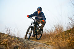 Enduro Cyclist Riding the Mountain Bike on the Rocky Trail. Extreme Sport Concept. Space for Text. Stock Images