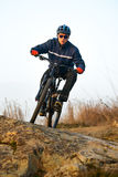 Enduro Cyclist Riding the Mountain Bike on the Rocky Trail. Extreme Sport Concept. Space for Text. Royalty Free Stock Image