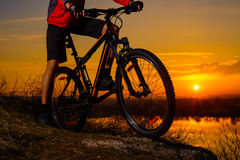Enduro Cyclist Riding the Mountain Bike on the Rocky Trail at Sunset. Active Lifestyle Concept. Stock Image