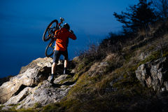 Enduro Cyclist Taking his Bike up the Rocky Trail at Night. Extreme Sport Concept. Space for Text. Stock Image