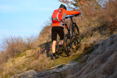 Enduro Cyclist Taking his Mountain Bike Up the Rocky Trail. Extreme Sport Concept. Space for Text. Stock Photo