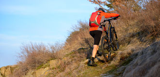 Enduro Cyclist Taking his Mountain Bike Up the Rocky Trail. Extreme Sport Concept. Space for Text. Royalty Free Stock Images