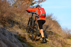 Enduro Cyclist Taking his Mountain Bike Up the Rocky Trail. Extreme Sport Concept. Space for Text. Royalty Free Stock Photo