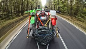 Enduro journey with dirt bike with the car on the road. Journey extreme trip with dirtbike in the mountain adn blue sky Royalty Free Stock Photo
