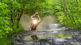 Enduro moto in the mud with a big splash Stock Images