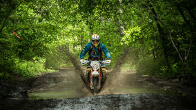 Enduro moto in the mud with a big splash Stock Photography