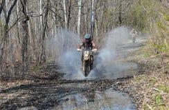 Enduro motorcycle rides through the mud with a big splash Stock Image