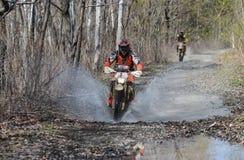 Enduro motorcycle rides through the mud with a big splash Stock Photos